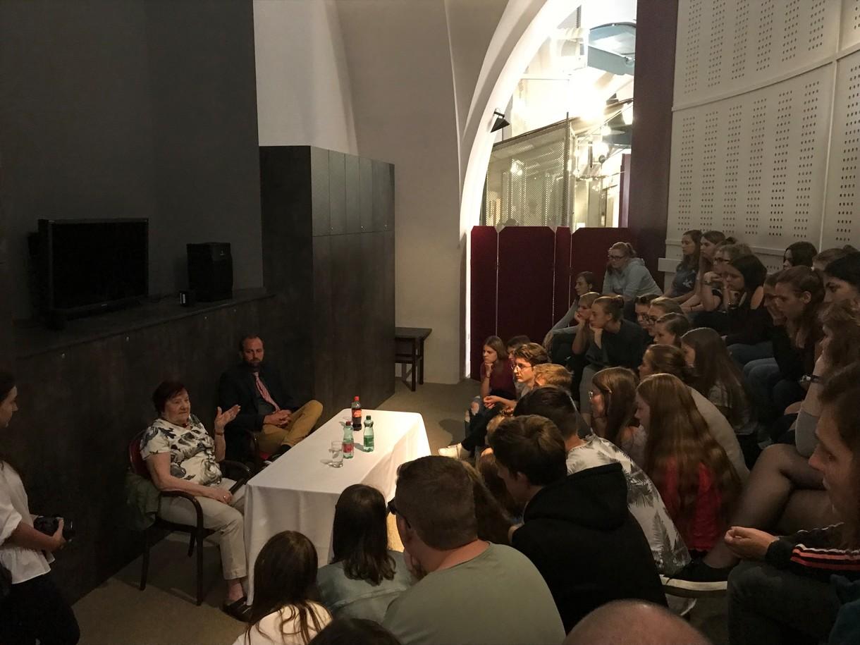 Anna Lehr Splawinski sitzt an einem Tisch mit Tischtuch vor dem Publikum, das man von hinten sieht.