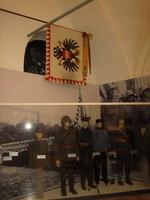 Schaufensterpuppen in Uniform vor Fotowand und unter Flagge mit Doppelkopfadler.