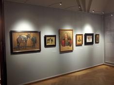 Wand mit mehreren gerahmten Gemälden und Zeichnungen.