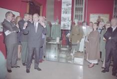 Besuchermenge zur Eröffnung der Sonderausstellung um eine Vitrine mit Uniformen stehend.