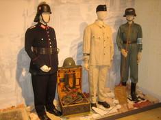 Drei Schaufensterpuppen mit verschiedenen Uniformen und Arbeitskleidern neben einem aufgeklappten Koffer.
