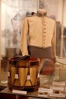 Trommel aus Holz, daneben Medaillen aus Blei und Silber und dahinter eine Uniformjacke.