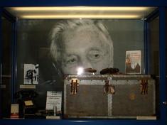 Vitrine mit Erinnerungsstücken und einer Kiste, als Rückwand ein Porträt von Carl Szokoll.