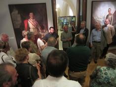 Kurator steht zwischen Gemälde des Kaisers und einer Besuchergruppe, die man nur von hinten sieht.