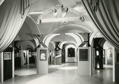 Ausstellungssaal mit Torbögen, Vitrinen und den Eingang verzierenden Vorhängen.