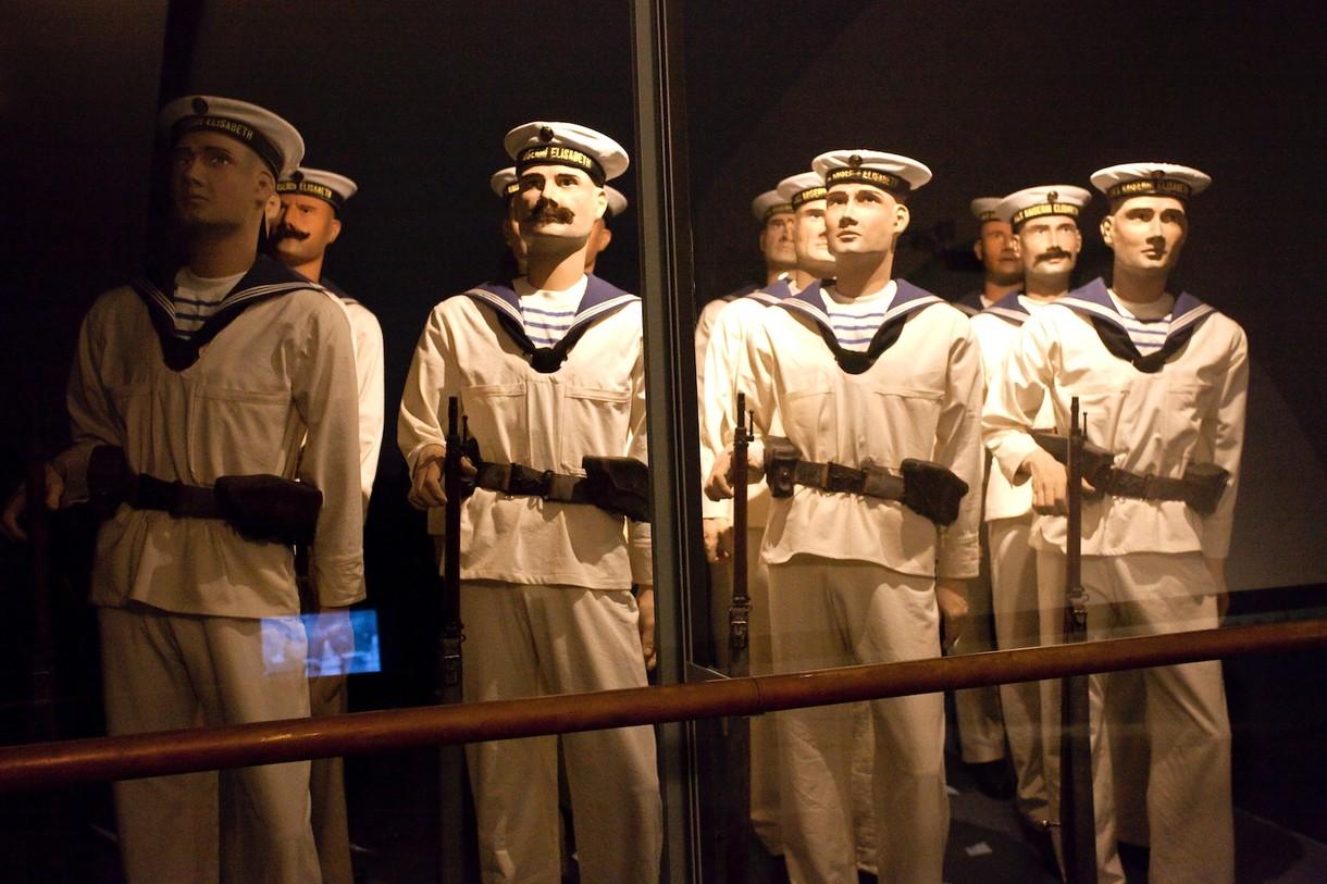 Männliche Schaufensterpuppen mit Matrosenkleidung in einer Vitrine.
