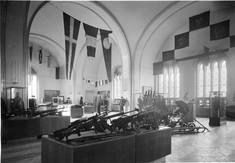 Schwarz-weiß-Foto mit Gewehren auf Schaukästen und Flaggen