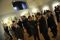 Besucher stehen im Raum, unterhalten sich und betrachten die Bilder.