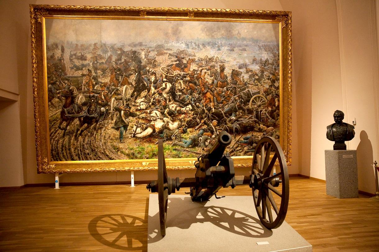 Gemälde mit Schlachtenszene, gestürzten Pferden und verletzten Soldaten, davor eine Feldkanone.