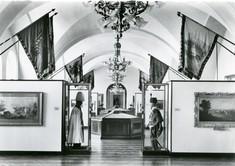 Schwarz-weiß-Foto mit Schauwänden mit Gemälden links und rechte, darüber Flaggen und davor zwei Schaufensterpuppen mit Uniformen.