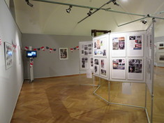 Ausstellungsraum mit Schautafeln mit Fotos und Infotexten, dazwischen Wimpel.