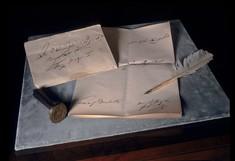 Brief, Federkiel und Siegelstempel auf einem Tisch.