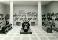 Artillerie auf Podesten am Boden, an der Wand Malereien mit Pferden und Kutschen.