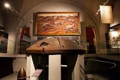 Panzerkuppel auf vier kleinen Säulen vor einem Gemälde.