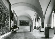 Blick in den Ausstellungsraum mit Gemälden an den linken Seitenwänden und Schaukästen vor den Fenstern rechts.