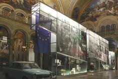Wand aus Glaskästen mit EU-Flagge und Plakaten, daneben ein Trabant.