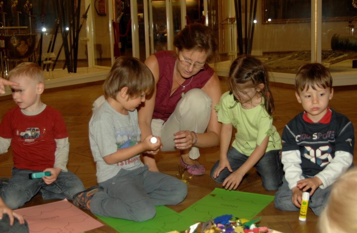 Kulturvermittlerin Monika Weber bastelt mit vier Kindergartenkindern am Boden mit Papier und Klebstoff.