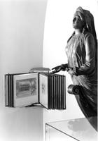 Schwarz-weiß-Foto eines aufgefächerten Fotoalbums und rechts davon eine  Gallionsfigur.
