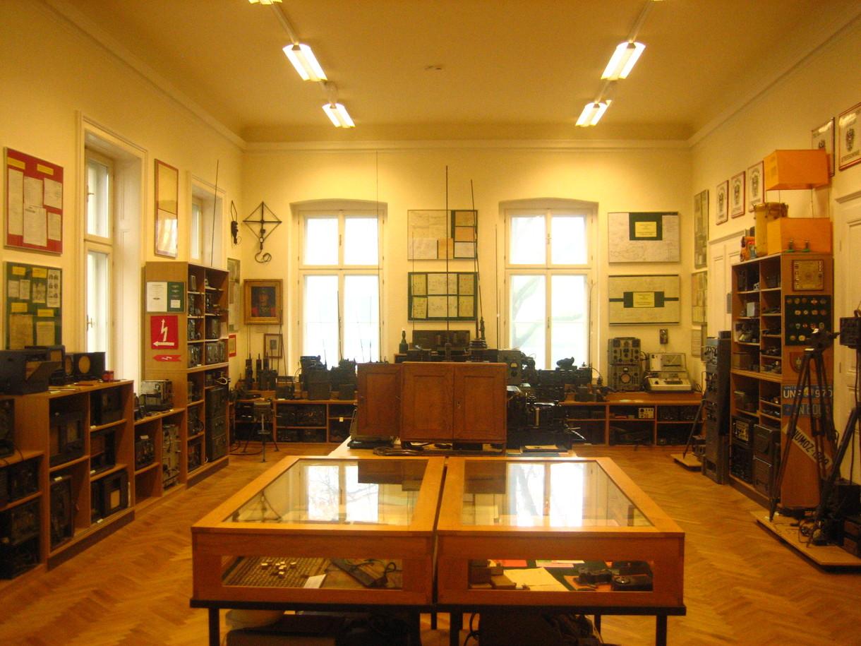 Ausstellungsraum in der Fernmeldesammlung mit niedrigen Holzregalen voller Fernmelder an der Wand entlang und Schaukästen in der Mitte.