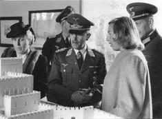 Drei deutsche Soldaten mit zwei Frauen blickend auf ein Architekturmodell.