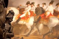 Statue eines reitenden Soldaten im Profil, dahinter ein Gemälde mit Schlachtenszenen.