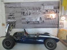 Historischer Rennwagen vor einem großen Bild von historischem Autorennen.