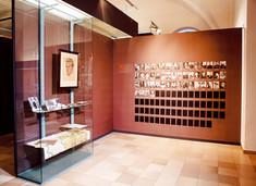 Vitrine mit verschiedenen Dokumenten, im rechten Winkel dazu eine Schauwand mit Fotos.