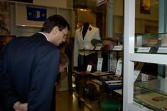 Mann im Anzug mit Brille schaut in eine Vitrine.