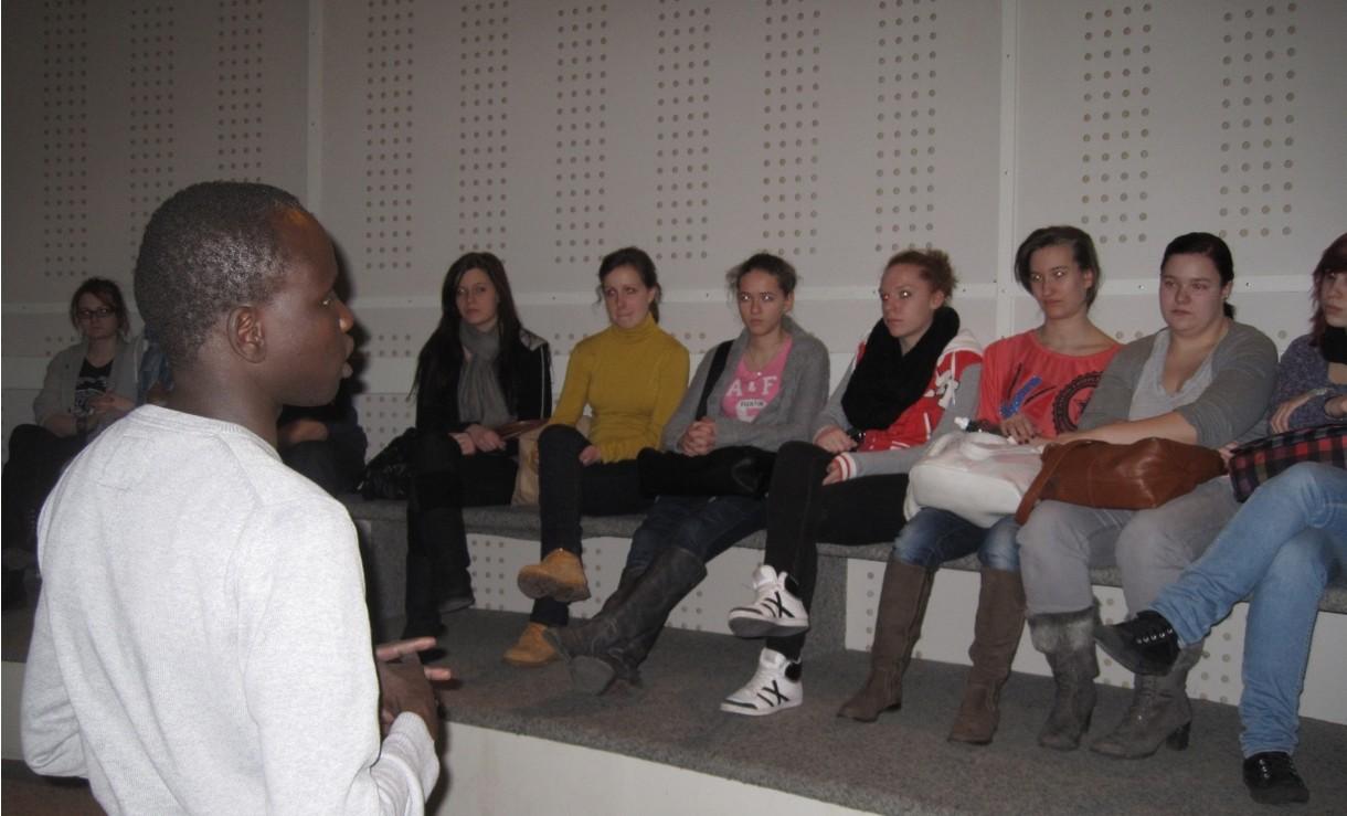 John Kon Kelei spricht vor einer Gruppe sitzender Jugendlicher.