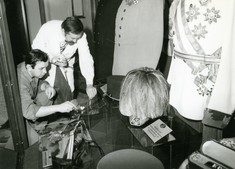 Zwei Männer beraten sich vor einer Vitrine mit Uniformen und Helmen. Einer trägt einen weißen Kittel.