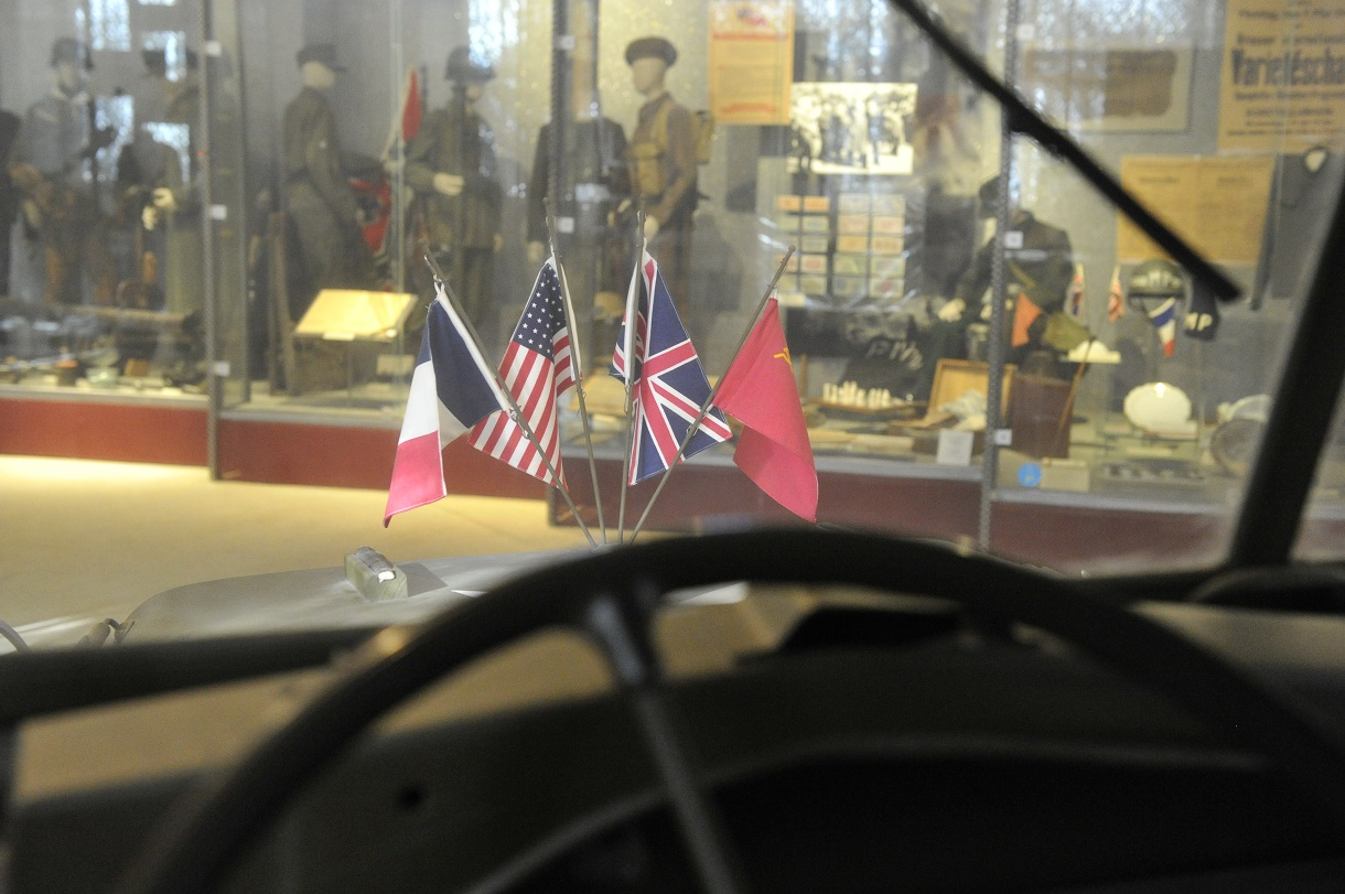 Blick aus einem Jeep auf die Fahnen von Frankreich, USA, der Sowjetunion und dem Vereinigten Königreich auf der Motorhaube.