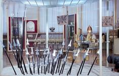 Verschiedene Schwerter und Stichwaffen stecken im Boden in einer Vitrine