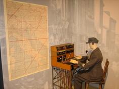 Schaufensterpuppe in Uniform sitzt am Funktisch vor einer Landkarte.