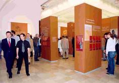 Mehrere Besucher gehen durch den Raum mit hölzernen Schauquadern, auf denen Plakate und Texte kleben.