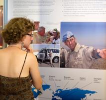 Besucherin steht vor einer Info-Tafel mit Text und Fotos.